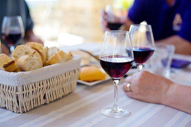 Sklenka červeného vína servírovaná s bagetou a sýrem