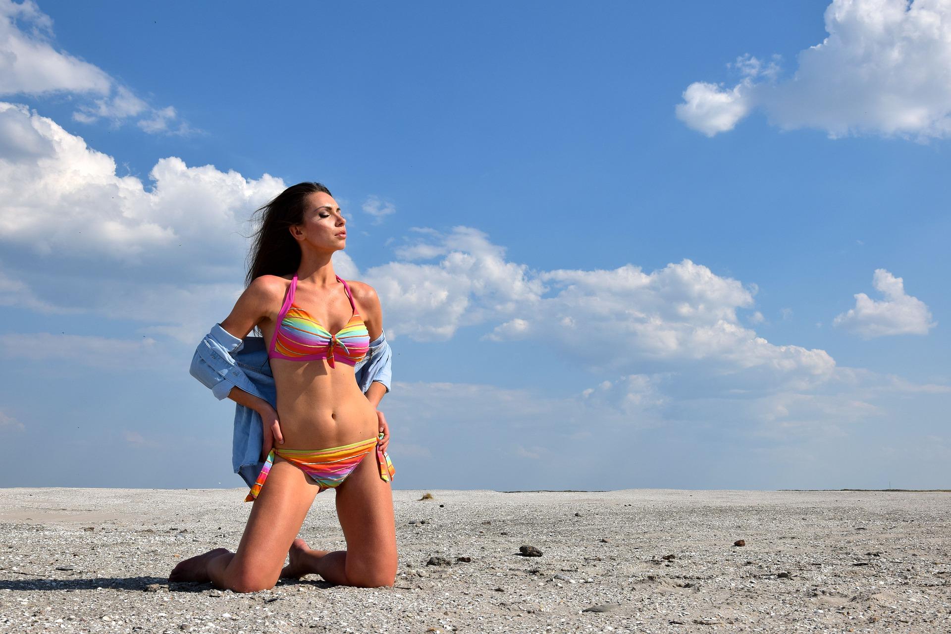 Štíhlá žena v plavkách na pláži.