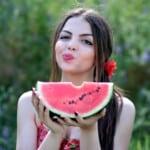 Dívka kousající vodní meloun.