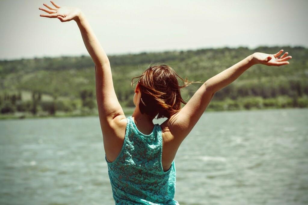 Šťastná žena na břehu jezera.