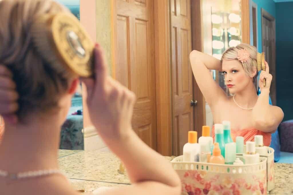 Žena si upravuje vlasy před zrcadlem.