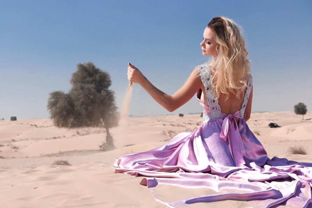 Blondýna na slunci v písku.