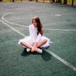 Dívka v šatech na sportovním hřišti.