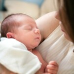 Spící kojenec v náruči matky.