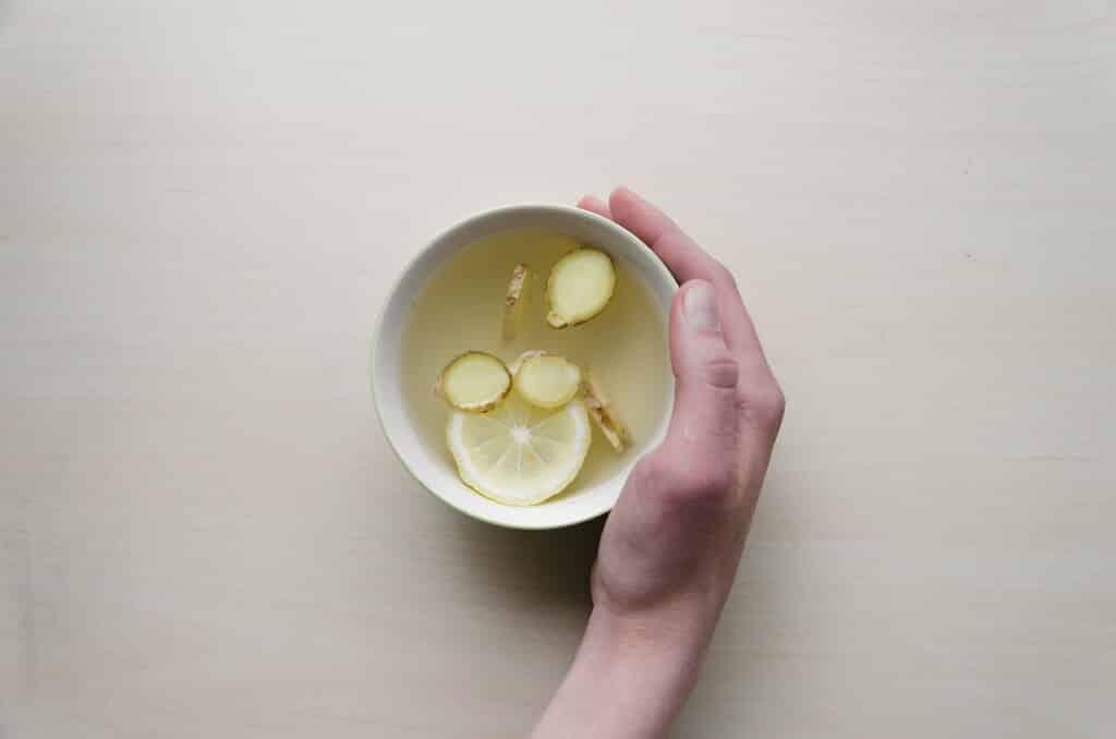 Miska se zázvorovým čajem a rukou.