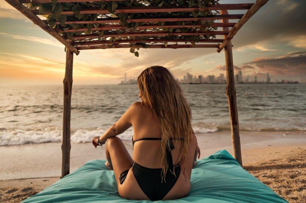 Žena v plavkách sedící na pláži.