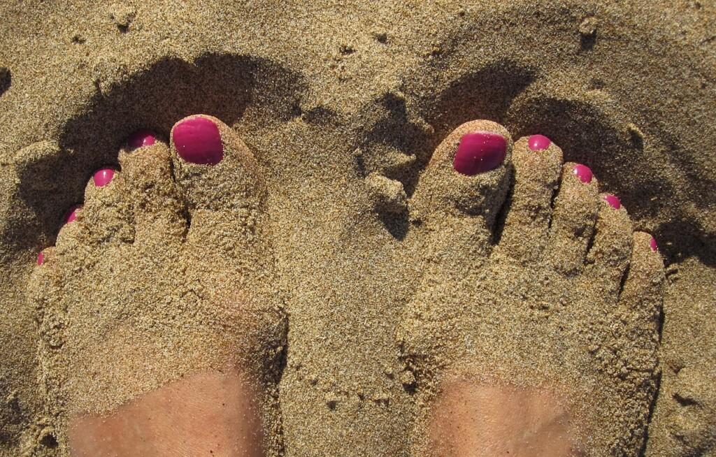 Nohy zahrabané v písku.