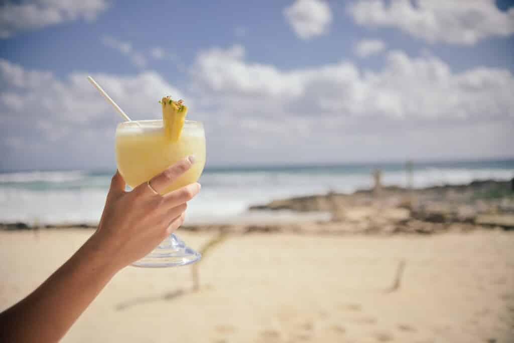 Koktejl ve sklenici na pláži.