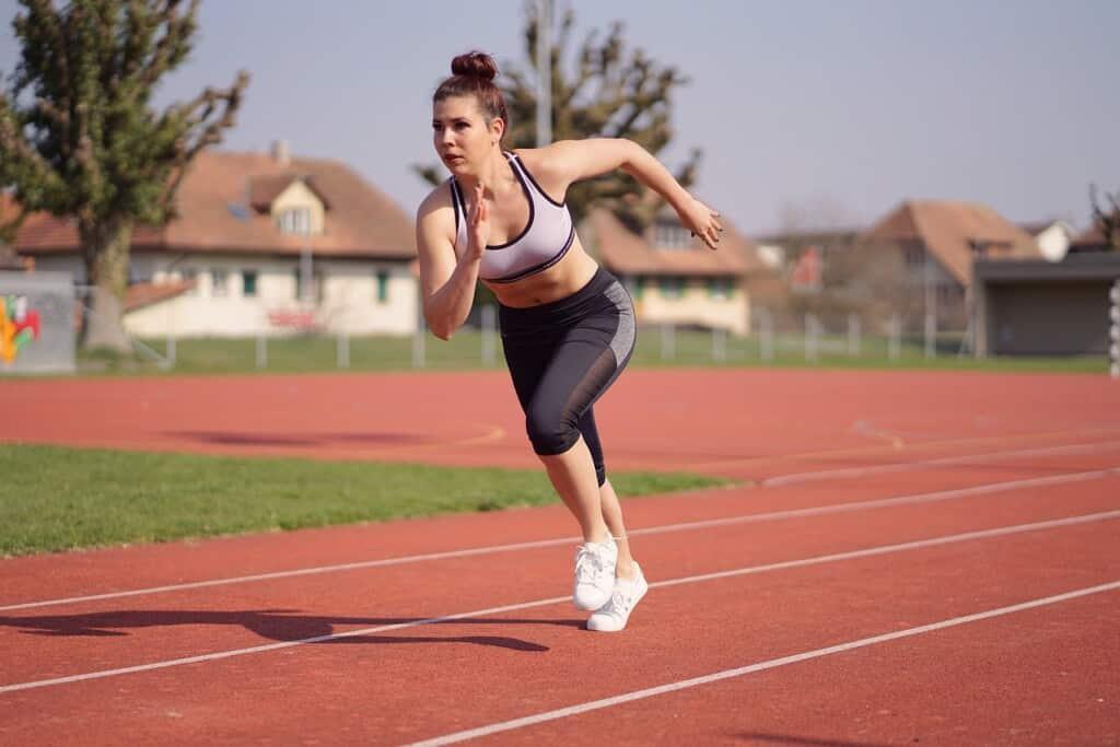 Žena běží po běžecké dráze.