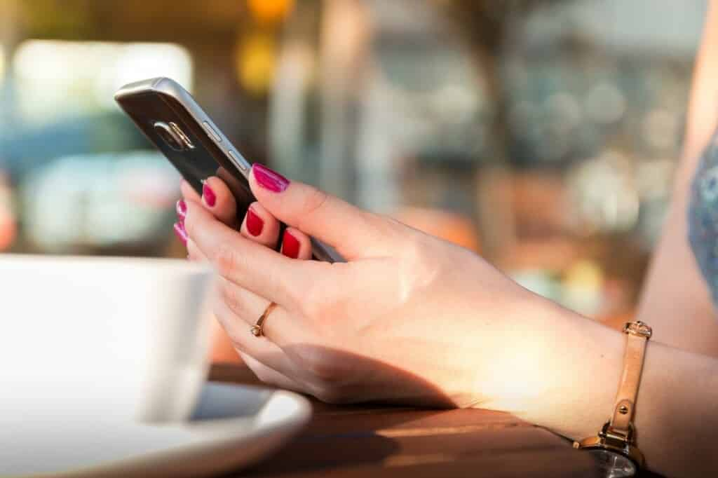 Ruce s rudými nehty drží telefon.