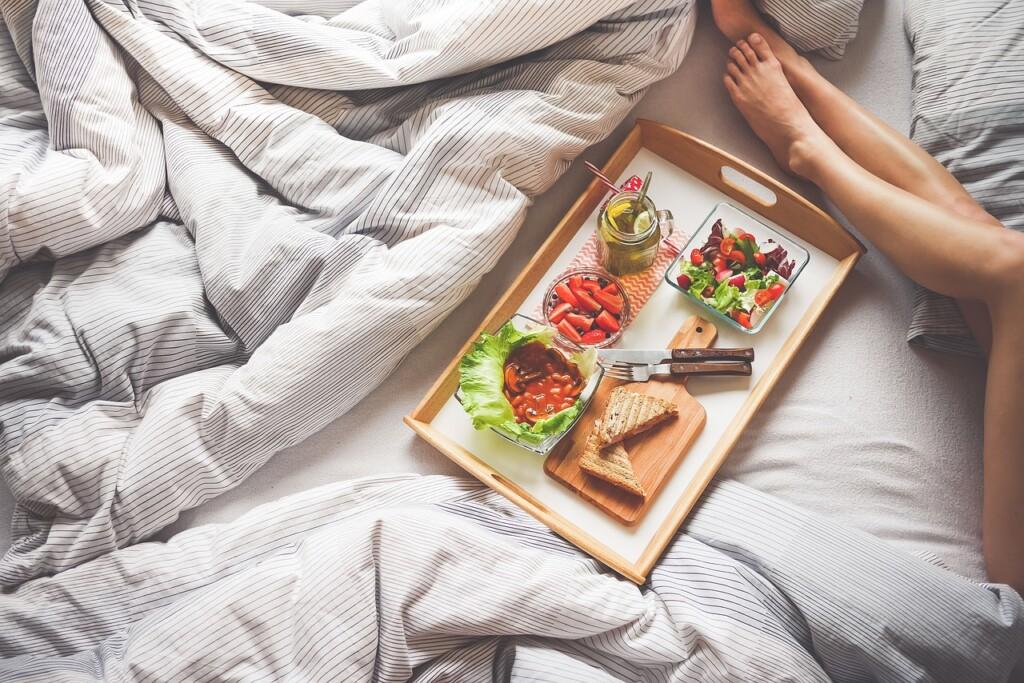 Tác s jídlem v posteli a nohy.