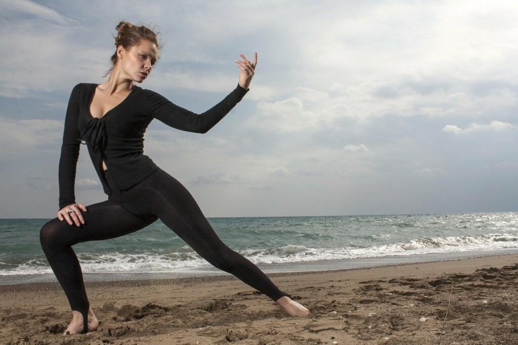 Dívka cvičí jógu na pláži.