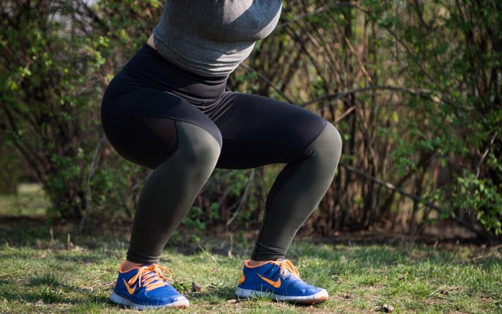 Žena v dřepu při cvičení.