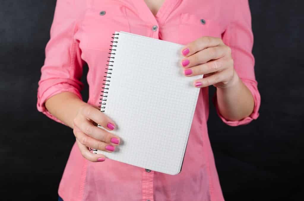 Žena v růžové košili se zápisníkem.