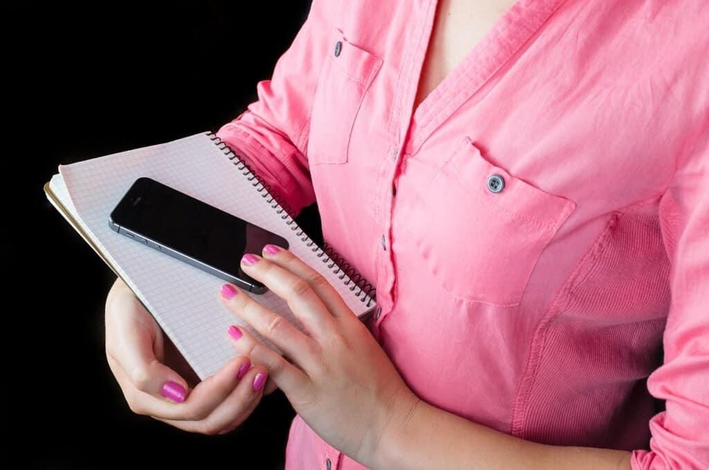 Žena v růžové košili s notesem a telefonem.