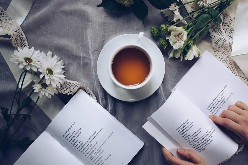 Šálek s čajem mezi květinami.