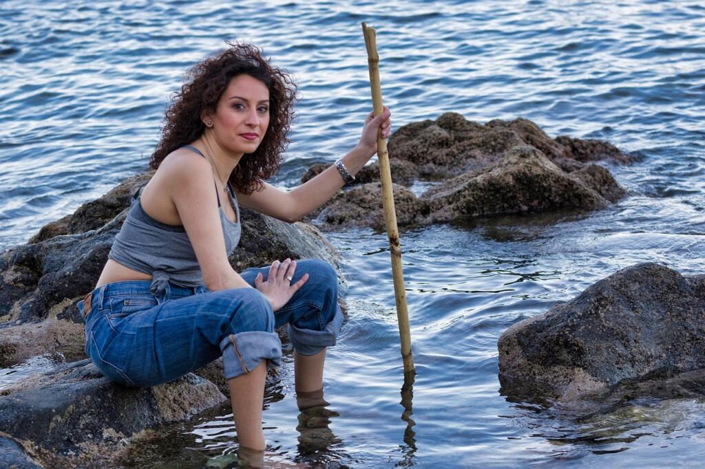 Žena s prutem na břehu moře.