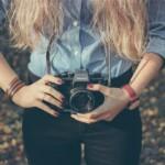 Dívka drží u pasu fotoaparát.
