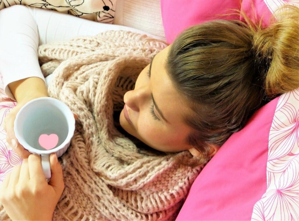 Nemocná žena leží s čajem v posteli.