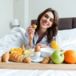 Žena snídající v posteli